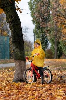 Мальчик стоит в парке со своим велосипедом в окружении желтых опавших листьев. осенний день. вертикальная рамка.