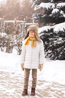 晴れた日に公園で冬に立っている少年