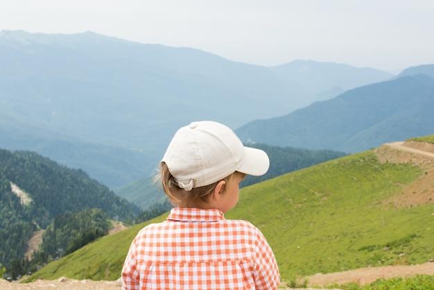 Мальчик стоит на скале в горах и смотрит вдаль. вид сзади