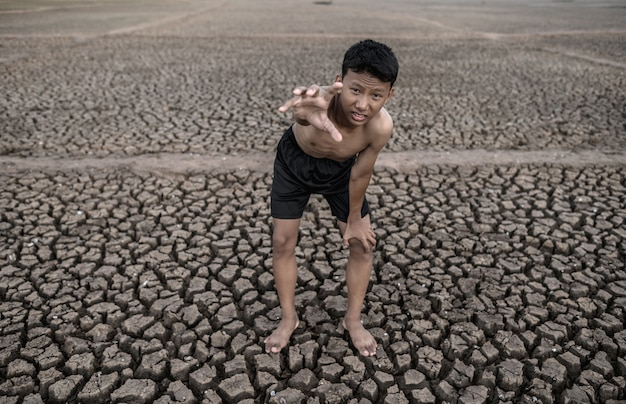 The boy stood bent on his knees and made a mark to ask for rain, global warming and water crisis. Free Photo