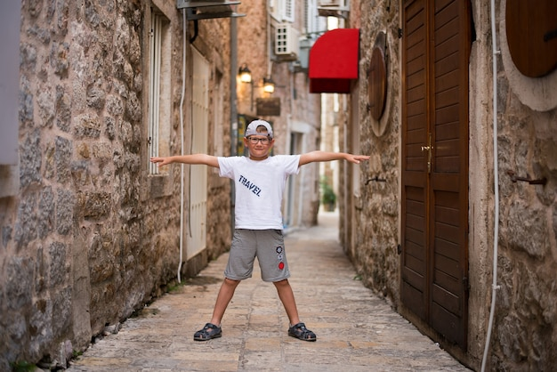The boy stretched his arms across the narrow street in the old city