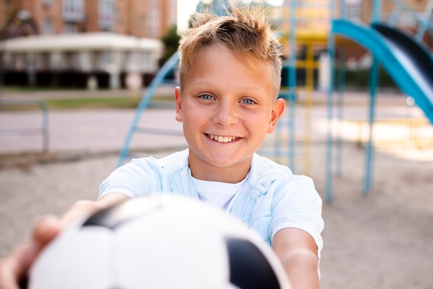 Boy stretching soccer ball to the camera