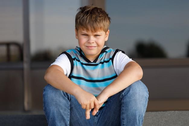 Полосатый джемпер мальчик сидит на ступеньках в парках