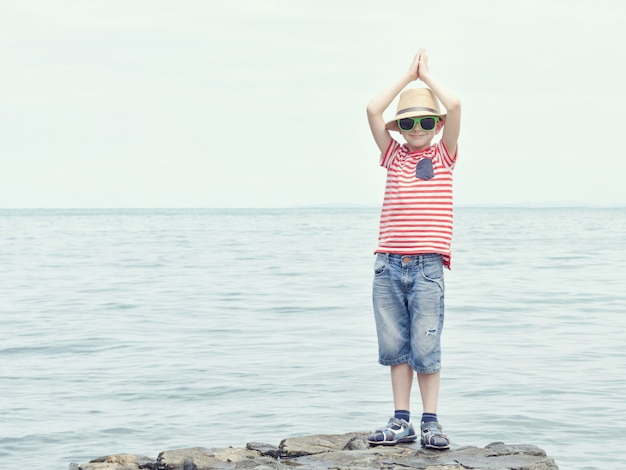 Boy in the striped t-shirt and sunglasses standing on stone. hands up, sea on the background