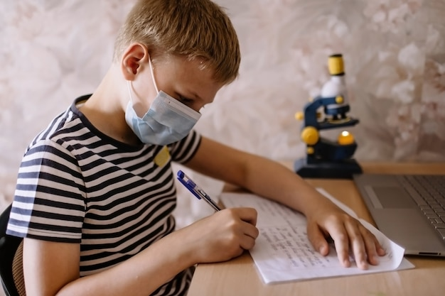Boy studies at home, wear protective mask, and doing school homework. distance learning online education.