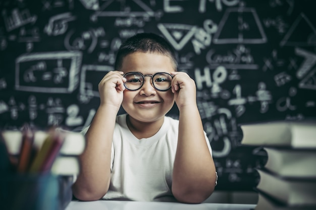 Boy studying and holding glasses leg in classroom.