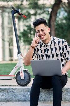 ノートパソコンとスクーターで公園で勉強している少年