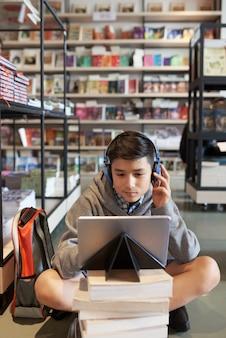 Мальчик учится в библиотеке
