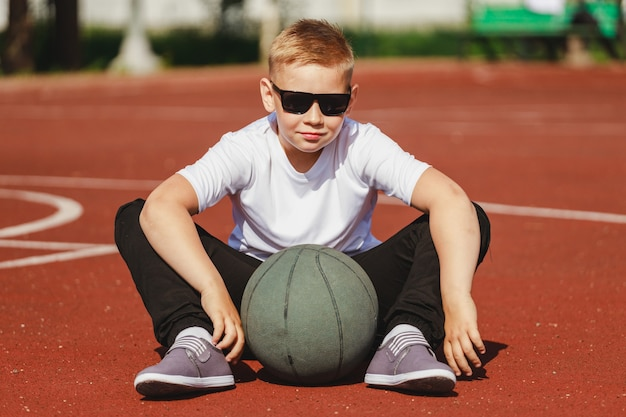 Boy in sunglasses sits on a basketball court with a ball in summer. high quality photo