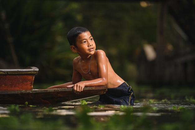 Boy swimming in the cannal near the damnoen saduak floating market