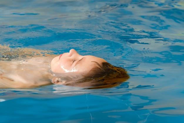 Мальчик плавает в крытом бассейне, развлекаясь во время урока плавания