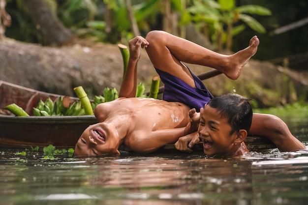 Damnoen saduak floating market 근처의 운하에서 수영하는 소년