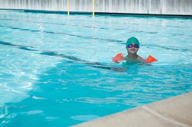 プールで泳いでいる少年