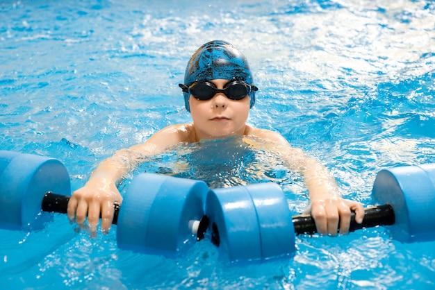 Мальчик плавает с водными гантелями в руках в бассейне