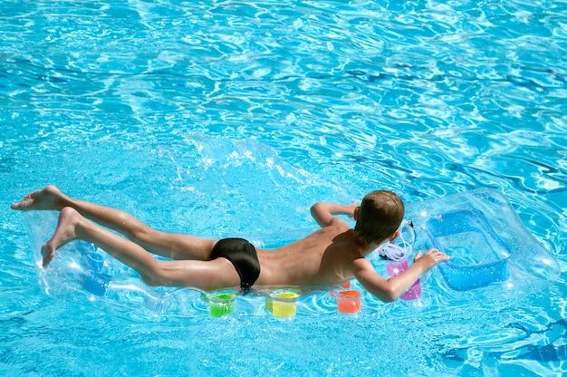 Мальчик плавает на надувном матрасе в чистой воде