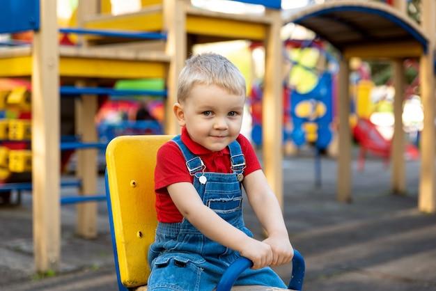 通りの遊び場でカルーセルを振る少年