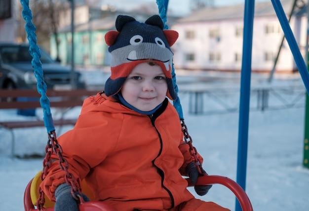 男の子は遊び場で冬の日にブランコでスイングします