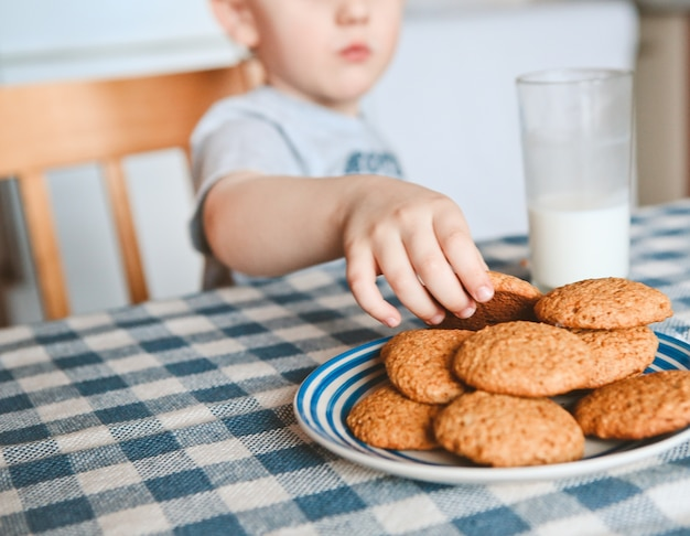 The boy at the table takes a small hand oatmeal cookies