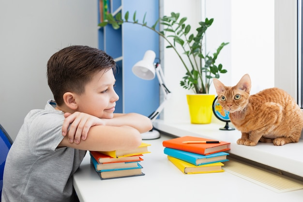 Boy at table with stack of books