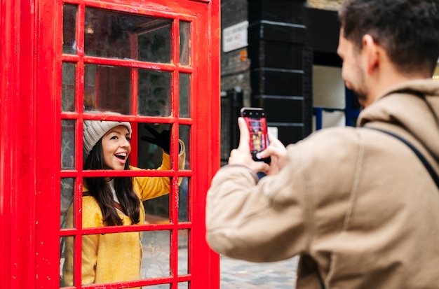 A boy takes a picture with the mobile phone of a girl in a yellow coat and a wool hat in a red cabin on a london street