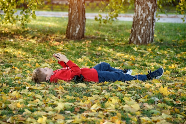 Boy takes pictures while lying on his back. lawn with autumn foliage. sunny day