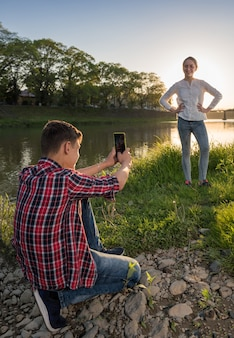 강 근처 공원에서 행복 하 게 웃는 여자의 소년 복용 사진. 여름 화창한 날
