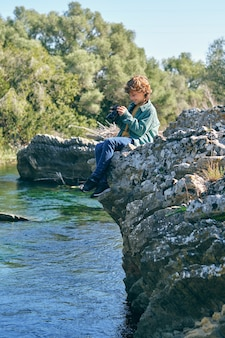 물 근처 바위 절벽에 앉아 사진을 찍는 소년