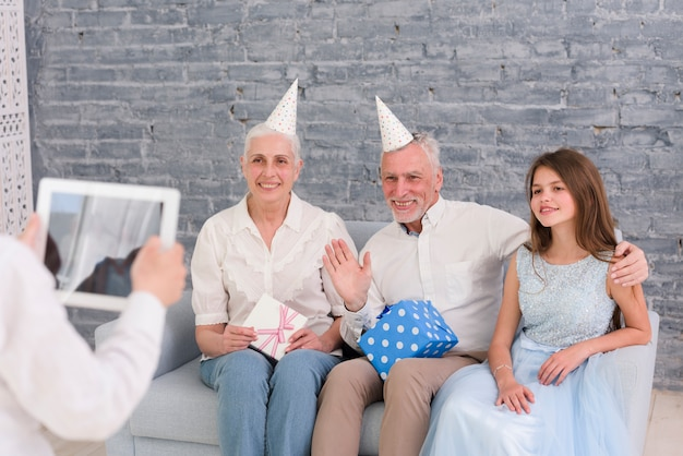 Boy taking photograph of his grandparents and sister sitting on sofa with digital tablet