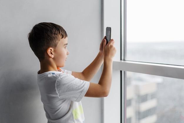 그의 휴대 전화로 사진을 찍는 소년