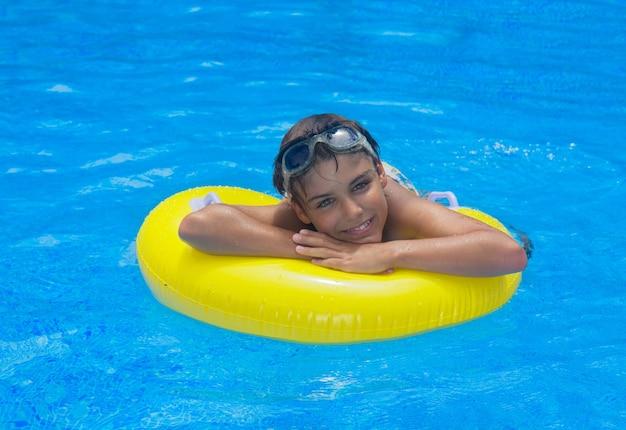 Boy taking sunbath in pool on rubber ring