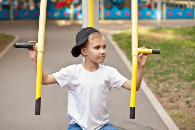 屋外の公園の遊び場でスポーツトレーニング器具を持った少年10代の子供。