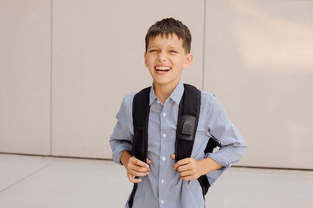 소년 십대 11세 남학생은 배낭을 메고 회색 배경에 있는 카메라를 보고 웃고 있습니다. 체크무늬 셔츠를 입은 프리미엄 사진