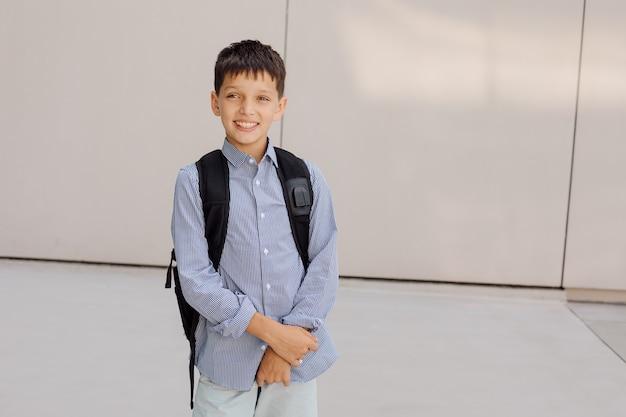 소년 십대 11세 남학생은 배낭을 메고 회색 배경에 있는 카메라를 보고 웃고 있습니다. 체크무늬 셔츠를 입은