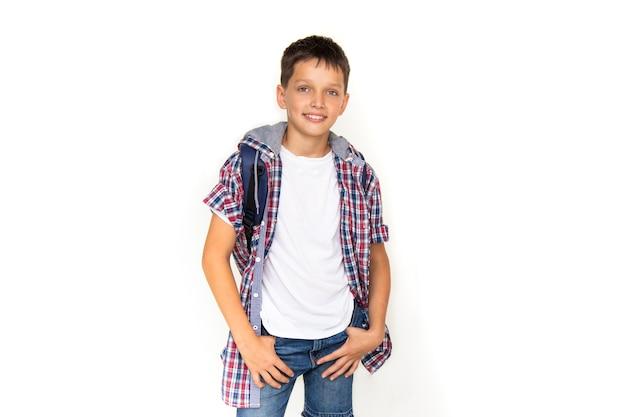 소년 십 대 11세 모범생 배낭과 흰색 배경에 카메라를 보고 웃 고. 격자 무늬 셔츠와 흰색 티셔츠를 입고 복사 공간