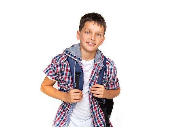 소년 십 대 11세 모범생 배낭과 흰색 배경에 카메라를 보고 웃 고. 체크무늬 셔츠와 흰색 티셔츠를 입고