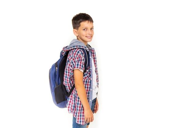 소년 십 11세 모범생 배낭과 흰색 배경에 미소로 카메라를 보고 웃 고. 격자 무늬 셔츠와 흰색 티셔츠를 입고 복사 공간