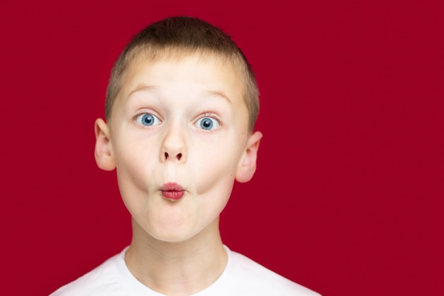 Boy teenager 7-10 in a white t-shirt makes faces, depicting a kiss, with wide open eyes on a red background