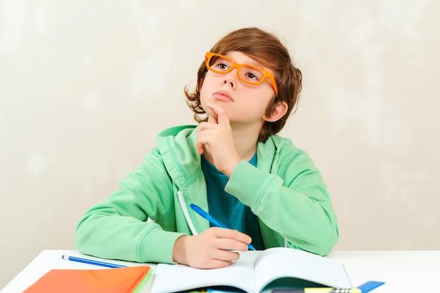 考えて宿題をしている少年。本を勉強して読んでいる小さな学生の男の子。宿題をしている眼鏡をかけたかわいい男子生徒。教育と新学期のコンセプト
