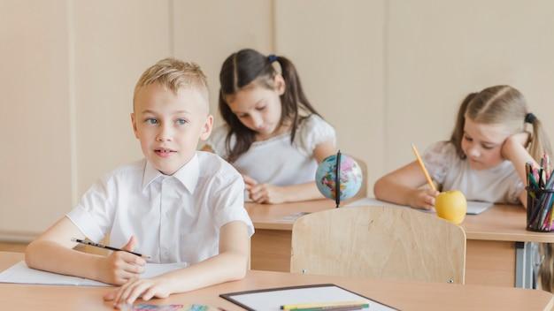 Мальчик думает и смотрит в сторону во время урока Бесплатные Фотографии