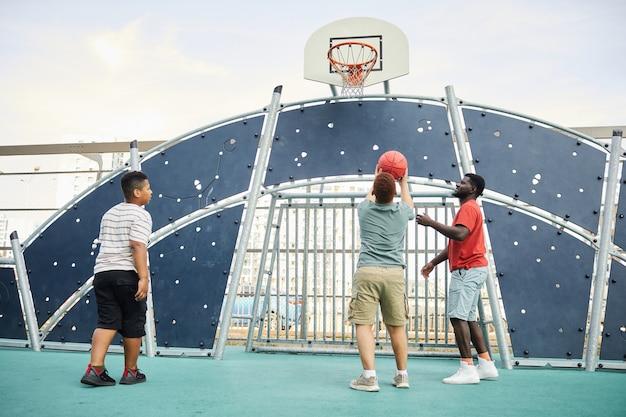 Мальчик бросает мяч в баскетбольное кольцо под контролем отца, играя в баскетбол с братом на спортивной площадке