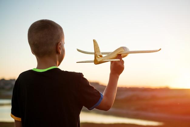 소년은 여름에 장난감 비행기를 던져 일몰에 아이가 장난감 비행기를 가지고 노는 여행을 꿈꿉니다.