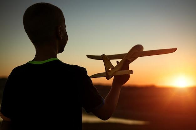 소년 일몰 여름에 장난감 비행기를 던졌습니다.