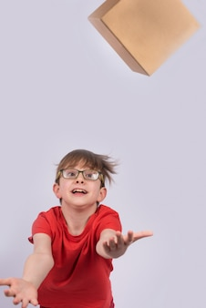 Boy throws box and catches it. photos in motion. vertical frame