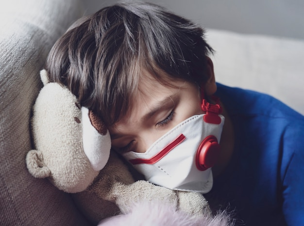 A boy tired from chest coughing wearing face mask for protect pm2.5,child falling sleep while playing with toy, kid stay at home for protection coronavirus,flu outbreak and illness protection concept
