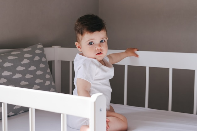 Boy toddler baby sitting on the bed in bedroom in white bodysuit