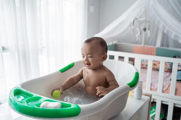 男の子の幼児はお風呂に入っている間水で遊びを楽しむ