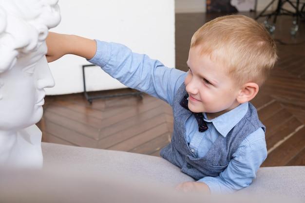 Мальчик касается гипсового бюста, лежа на диване