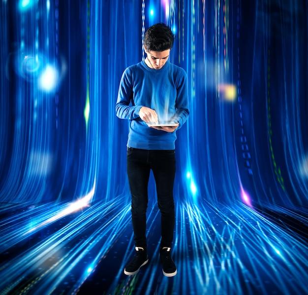 배경 조명으로 태블릿 화면을 터치하는 소년