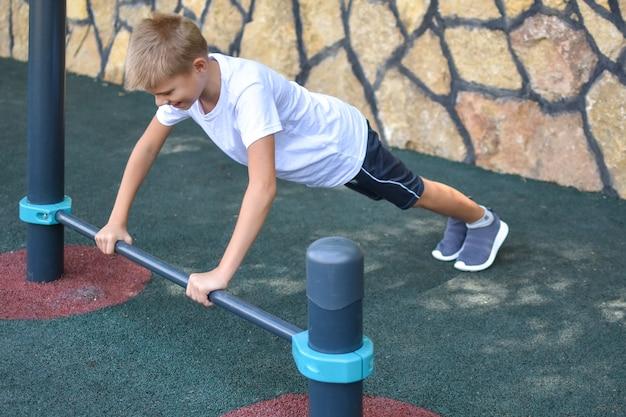 Мальчик тренируется на тренажере под открытым небом. спортивный ребенок летом на детской площадке.