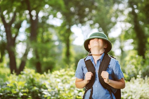 Мальчик-путешественник в шлеме играет в парке.
